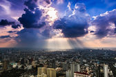 Rays of light shining through dark clouds city — Stock Photo