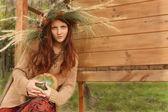 Girl in an autumn wreath with pumpkin — Stock Photo