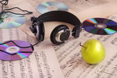 Headphones, CDs, sheet music and apple — Stock Photo