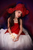 Girl in a red hat with a rose on a dark background — Stock Photo