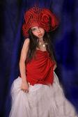 Bir gül karanlık bir arka plan üzerinde kırmızı şapkalı kız — Stok fotoğraf