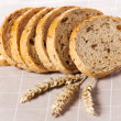 Healthy whole grain sliced bread with sunflower seeds on brown n — Stock Photo