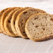 Healthy whole grain sliced bread with sunflower seeds on brown n — Stock Photo #21599405