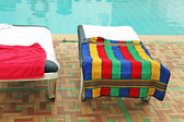 Relax chairs near the pool with towels — Stock Photo