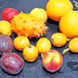 Exotic fruits: orange, kiwano, loquat, peach and passionfruit — Stock Photo