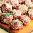 Raw meatballs on the chopping board - Stock Photo