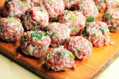 Raw meatballs on the chopping board — Stock Photo