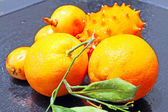 Exotic fruits: orange, kiwano and loquat — Stock Photo