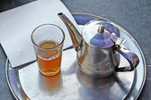 A kettle of moroccan mint tea and a glass — Stock Photo