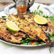 Grilled fish with greens on the plate - Stock Photo