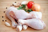 Raw chicken legs with vegetables and spices on the chopping boar — Stock Photo