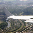View from airplane of the wing and a land beneath — Stock Photo