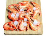 Fresh red shrimps with ice on the chopping board — Stock Photo