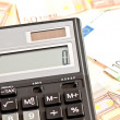 Business picture: money and calculator - Stock Photo