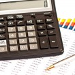 Business picture: calculator, financial graphs, pen — Stock Photo #25552311