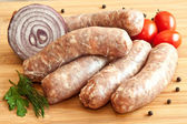 Uncooked sausages with vegetables on the chopping board — Stock Photo