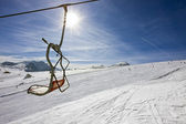 Vacant chair of a ski-lift above a ski slope — Stock Photo
