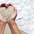 Mellow heart shaping female hands above beach — Stock Photo