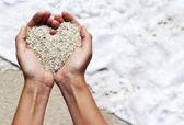 Dulce corazón formar manos femeninas sobre la playa — Foto de Stock
