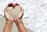 Mellow heart shaping female hands above beach — ストック写真