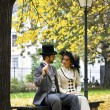 Old-fashioned dressed couple on park bench in fall. — Stock Photo #28219711