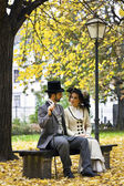 Old-fashioned dressed couple on a park bench in fall. — Stock Photo