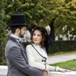 Old-fashioned dressed couple in park — Stock Photo #28221361