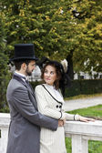 Old-fashioned dressed couple in the park — Stock Photo