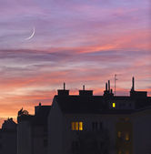Sunset over urban rooftops with lights from some home windows. — Foto de Stock