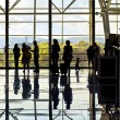 Stock Photo: Silhouettes of unrecognizable traveling people at the airpor