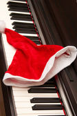 Piano key with santa hat on a white background. — Stock Photo