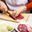 Closeup of woman hands cutting beef on cutting board. — Stock Photo #27578433