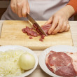 Closeup of woman hands cutting beef on cutting board. — Stock Photo #27578527