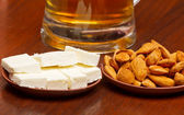Almonds, sheep cheese against beer — Stock Photo