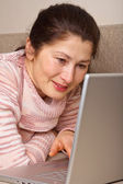 Senior woman with laptop, relaxing on the couch. — Foto de Stock