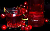 Glass with cherry isolated on a black background. — Stock Photo