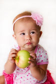 Baby girl eating a green apple — Stockfoto