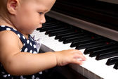 Baby girl playing the piano — Stock Photo
