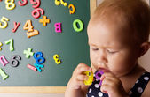 Funny baby girl playing with letters — Stock Photo