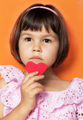 Little girl and red hearts. — Stockfoto