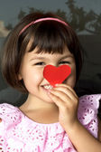 Little girl and red hearts. — Stock Photo