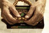Yaşlı kadının elinde tespih tutan — Stok fotoğraf