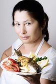 Female chef shows sea bream fish — Stock Photo