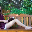 Pretty teen girl reading outside on a bench - copyspace — Stock Photo