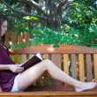 Pretty teen girl reading outside on a bench - copyspace — Stock Photo #13135079