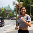 Fit young woman running on a busy city street — Stock Photo #29230041