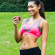 Foto de Stock  : Fit young womwith apple in park
