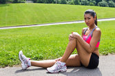 Young woman with running injury on knee — Stock Photo