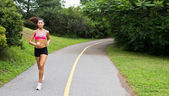 Smiling young woman running for fitness — Stok fotoğraf