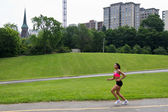 Fit woman running in the city park — Stock fotografie
